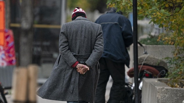 Deux hommes de dos sur un trottoir.