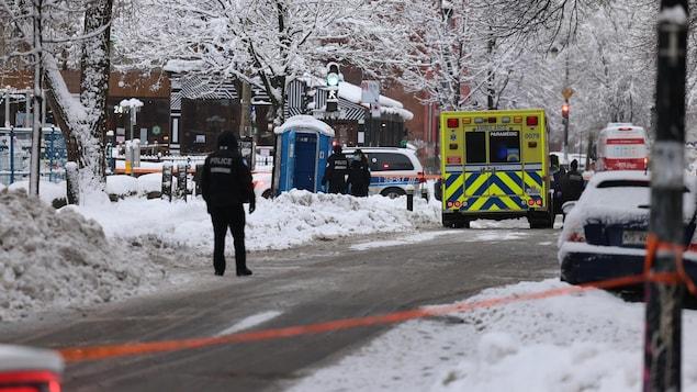 Une ambulance et des policiers près d'une toilette mobile dans une rue enneigée.