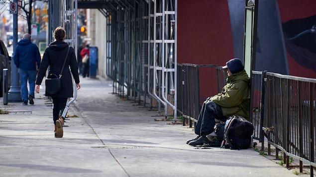 Un sans-abri regarde passer des passants.