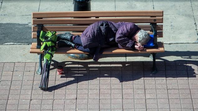 Une femme est allongée sur un banc de trottoir à Ottawa.