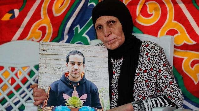 La mère d'Iyad Hallak tient dans ses mains une photo de son fils. On le voit tenir un pot de fleur.