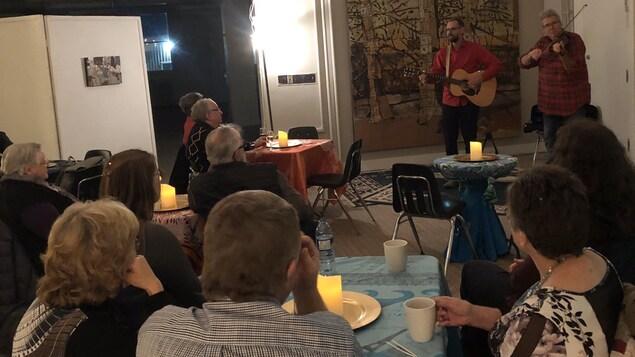 Deux musiciens font un spectacle de musique devant plusieurs personnes.