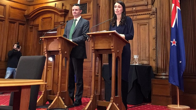 Un homme et une femme derrière un pupitre