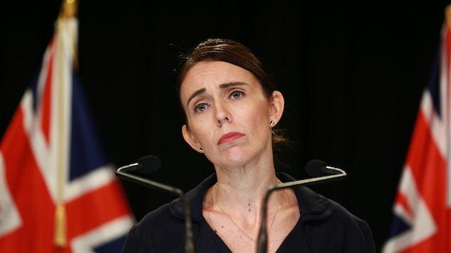 Une femme à la mine sérieuse semble écouter une question d'un journaliste lors d'un point de presse.