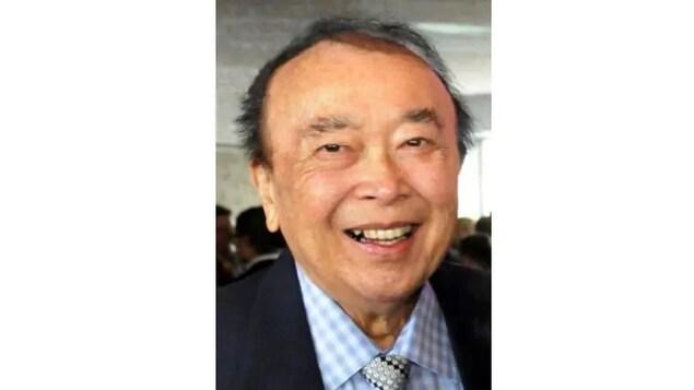 Un vieil homme asiatique en complet cravate sourit.