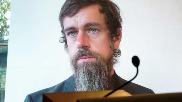 Le visage de l'homme apparaît sur un écran géant alors qu'il participe à une rencontre par visioconférence.