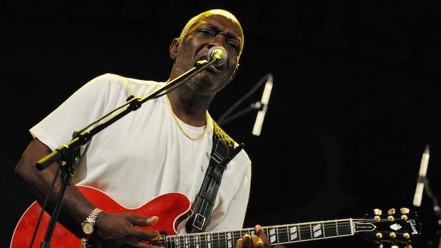 Un homme joue de sa guitare rouge en chantan dans un micro, avec un batteur en arrière-plan.