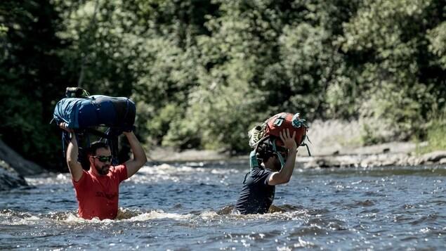 Jacob Racine traverse une rivière à pied dans le cadre d'une expédition.