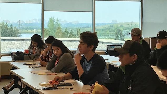 Les jeunes sont assis en classe.