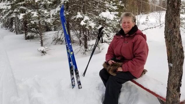 Une femme est assise sur un banc, dans la forêt, ses skis de fond plantés dans la neige à côté d'elle.