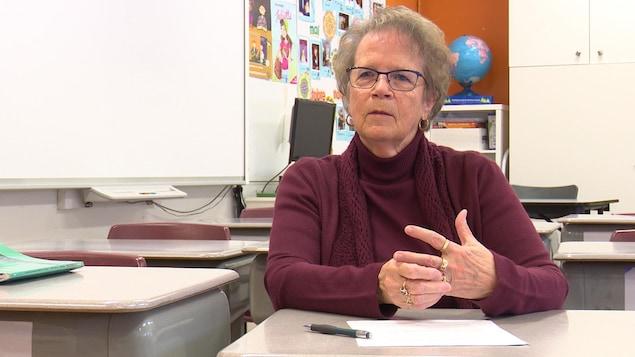 Une femme âgée est assise dans une salle de classe.