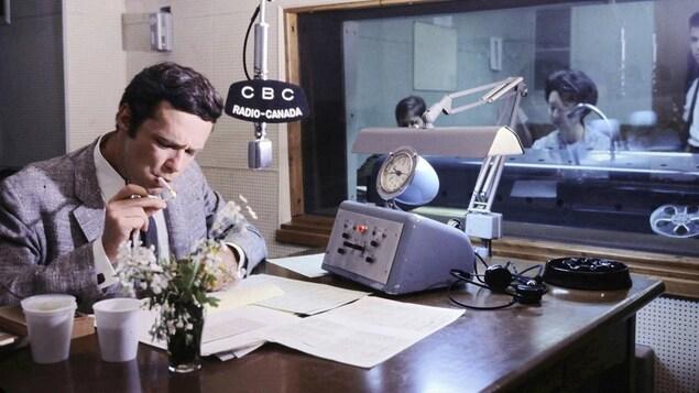 Dans un studio de radio, l'animateur Jacques Boulanger est assis à un pupitre et il révise ses notes tout en s'allumant une cigarette. Un micro est suspendu au-dessus de la table où repose un appareil de contrôle. À l'arrière-plan, on voit la réalisatrice Huguette Paré qui est derrière une vitre, dans la régie.