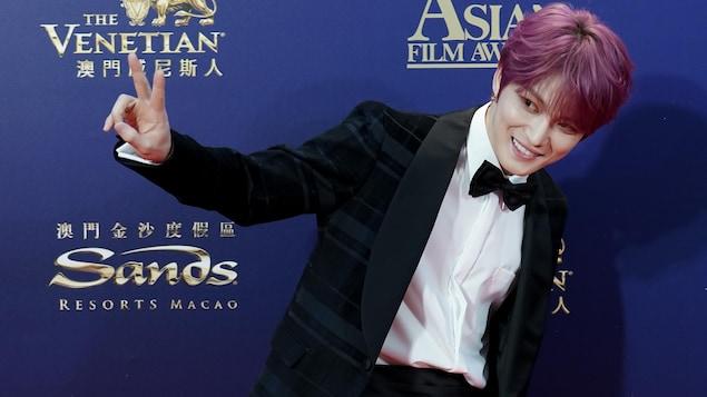 Un jeune homme en costume de gala, avec les cheveux roses, fait un signe de paix avec ses doigts.