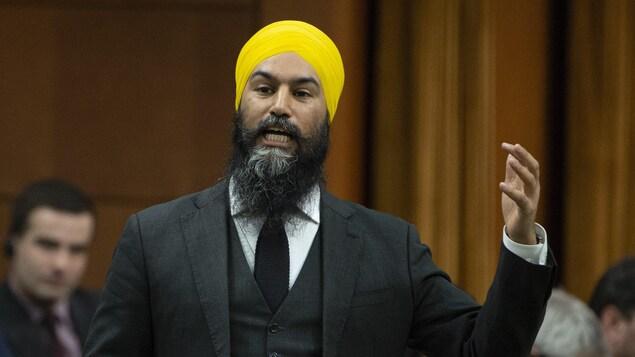 Jagmeet Singh, debout, lève le bras en posant une question à la Chambre des communes.