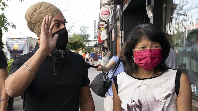 Jagmeet Singh salue quelqu'un. Il marche avec Olivia Chow sur un trottoir. Tous deux portent un masque.