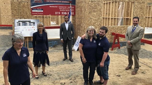 Six personnes sont devant une structure de bois d'un immeuble en construction.