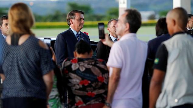 Quelques personnes entourant un homme en costume cravate