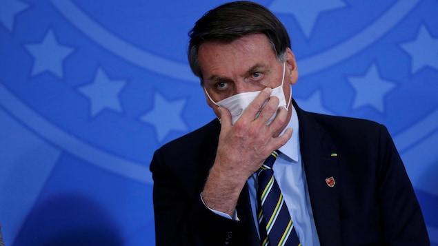 Jair Bolsonaro tient son masque avec une main.