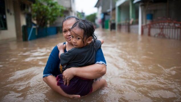 Une mère et sa fille marche dans une rue inondée.