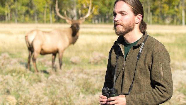Jake Paleczny, des jumelles à la main, devant un caribou qui est en flou, en arrière plan.