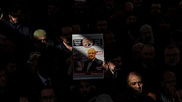 Au beau milieu d'une foule, un homme tient bien en évidence une affiche sur laquelle on voit une photo de Jamal Khashoggi.