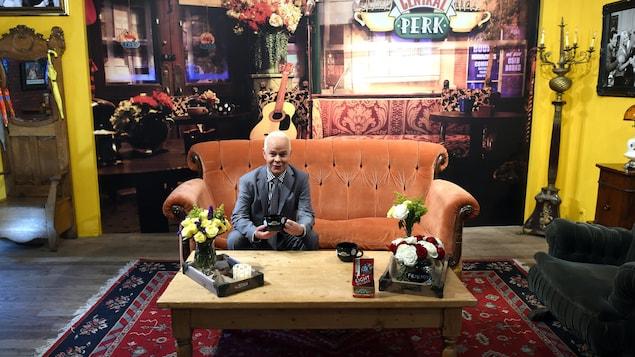 James Michael Tyler assis sur un divan orange dans un café.
