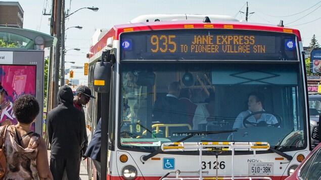 Des usagers montent à bord d'un autobus.