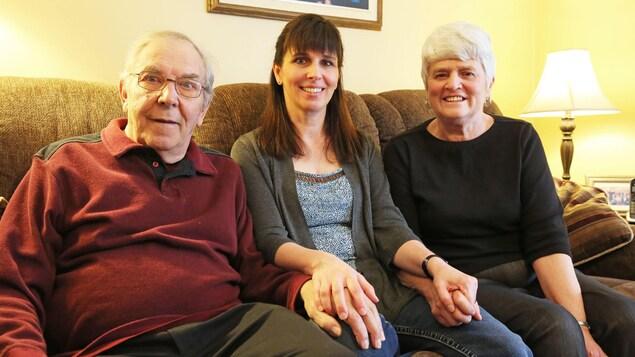 Les trois personnes assises sur le canapé de leur maison.