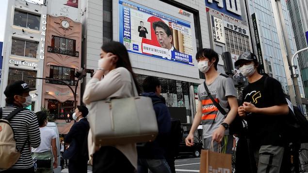Des Japonais portant des masques à l'extérieur.
