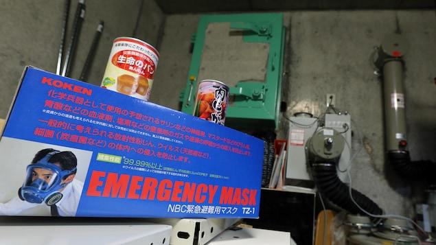 La boîte d'un masque à gaz sur laquelle il est écrit «masque d'urgence» à l'intérieur d'un abri sous-terrain en béton à l'intérieur duquel se trouvent aussi des boîtes de conserve d'aliments et des machines de purification d'air.