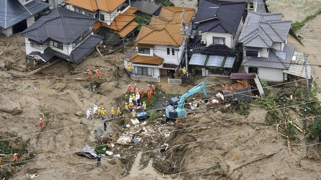 Des membres d'équipes de secours devant des débris de maisons détruites par des coulées de boue et des glissements de terrain.