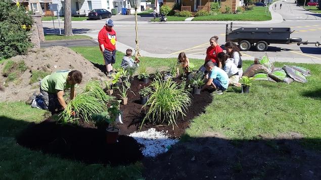 Des jeunes en train de jardiner.