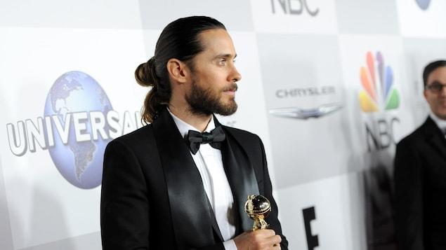 Un homme habillé en smoking pose pour une photo Oscar en main devant une bannière portant les logos des commanditaires d'un festival.