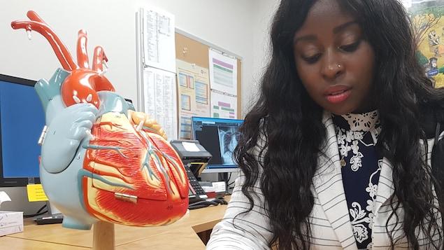 Jasmine Gitego regarde des éléments d'un coeur mécanique