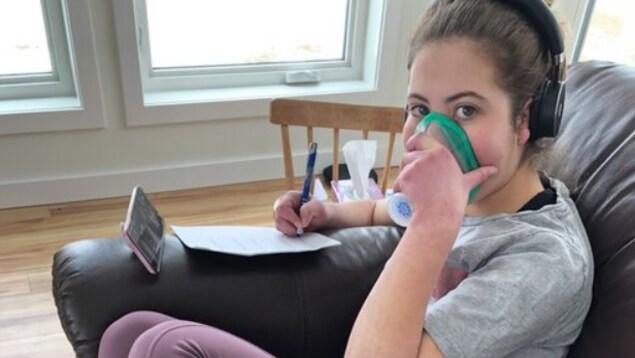 Jasmine Lambert utilise un appareil lui permettant de nettoyer ses voies respiratoires.