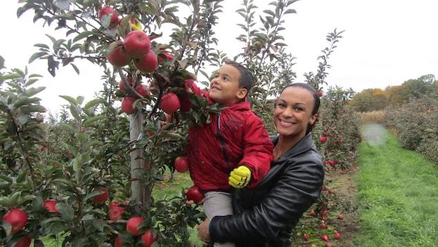 Une femme tient son fils dans ses bras dans un verger