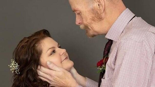 Les nouveaux mariés se regardent affectueusement dans les yeux. Jason Court tient tendrement les deux joues de Jennifer May.