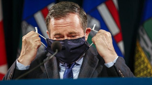Jason Kenney enlève son masque.