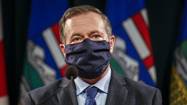 Plan rapproché de Jason Kenney en conférence de presse. Il porte un masque.