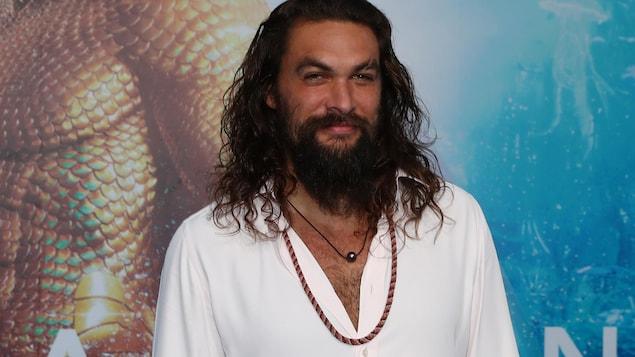 L'acteur souriant devant l'affiche du film Aquaman.