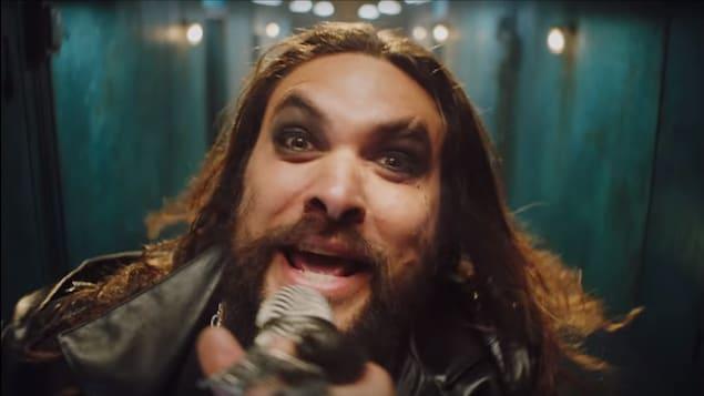 Un chanteur au style gothique chante dans le micro en regardant la caméra.