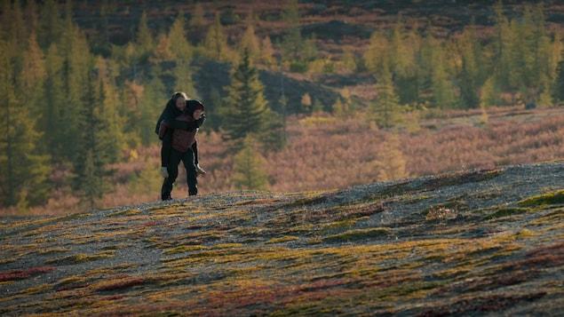 Une personne en porte une autre sur son dos.