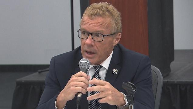 Un homme en veston, assis derrière une table, tient un micro en parlant au public.