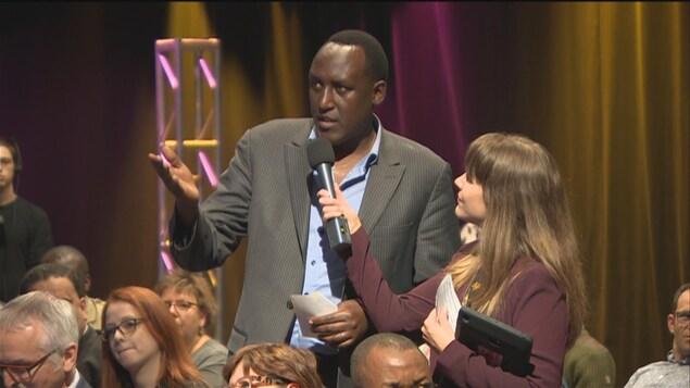 Le porte-parole du CPIP, Jean de Dieu Ndayahundwa, dans le public  pose une question lors du débat pour la présidence de l'ACF aux côtés de la journaliste Audrey Paris.