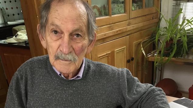 Jean Dumontier pose assis dans une cuisine.