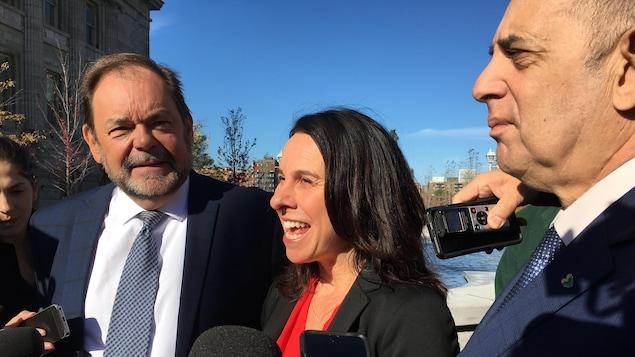 De gauche à droite : Jean Fortier, de Coalition Montréal, Valérie Plante, chef de Projet Montréal, et Marvin Rotrand, chef de Coalition Montréal, en conférence de presse à la place Vauquelin, près de l'hôtel de ville.