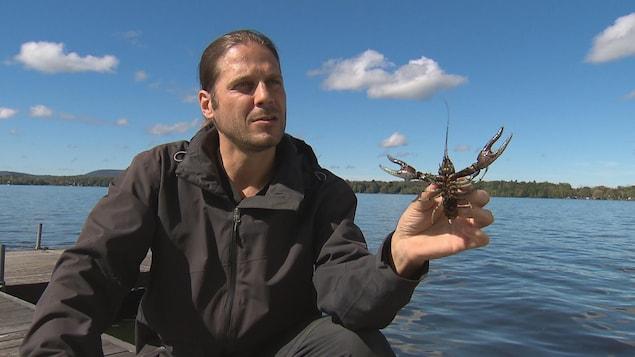 On voit M. Desroches, au bord d'un lac, qui tient une écrevisse dans sa main.