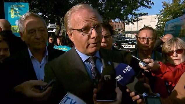 Jean-François Lisée entouré de plusieurs personnes, dans un point de presse.