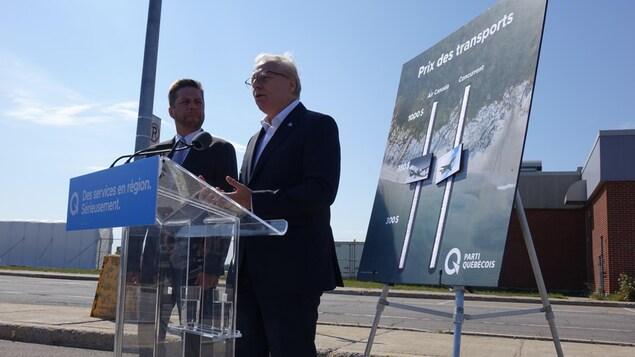 Jean-François Lisée est en point de presse devant l'aéroport de Baie-Comeau. Il est avec son candidat local et appuie son discours grâce à une affiche.