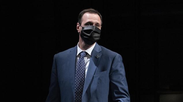 Le ministre de l'Éducation du Québec, Jean-François Roberge, debout et portant un couvre-visage devant un fond noir.